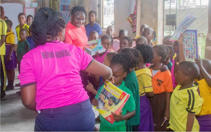 Sharing books donated to pupils of Ajiran community school Lekki