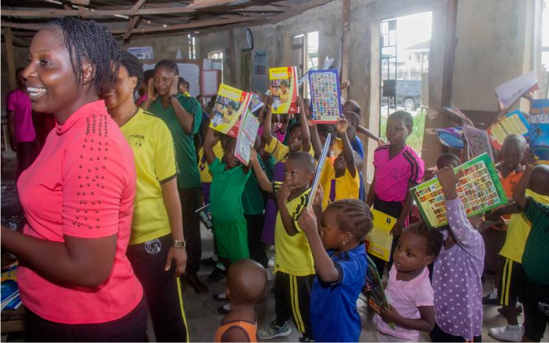 school children in lekki raising up books donated by Archvision Workgroup and Connect Group of Elevation Church