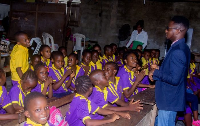 primary school children listening to a career talk from Tosin Ikuyiminu